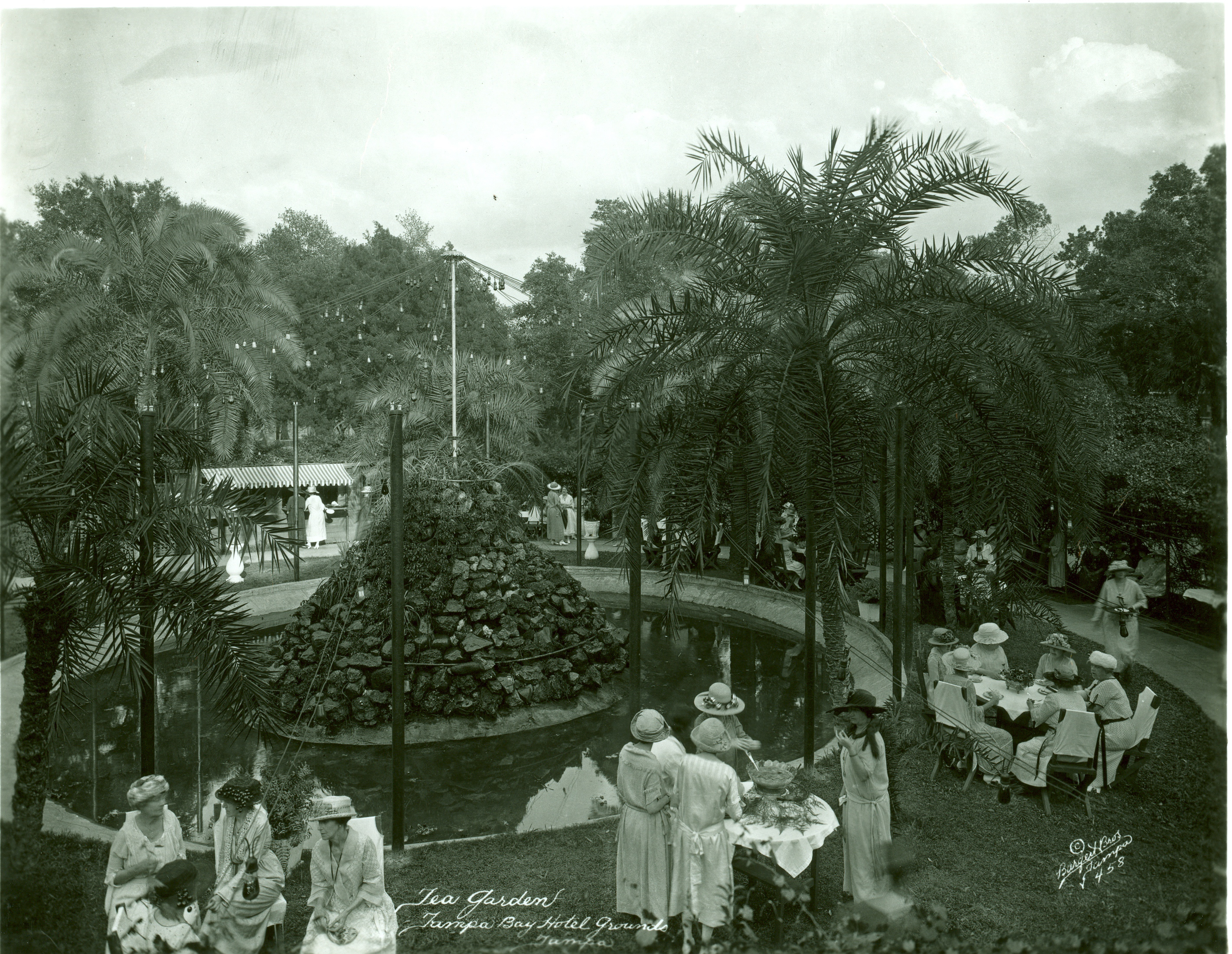 tea garden at Hotel, small round tables with 4-5 ladies at each, fancy dress, large rock fountain in center, lush greenery