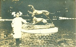 young girl next to statue of 2 hunting dogs. statue is on a pedestal, making it taller than the girl