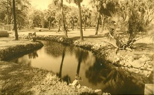 historic photo of creek winding through a park. trees and grasses on both sides of creek