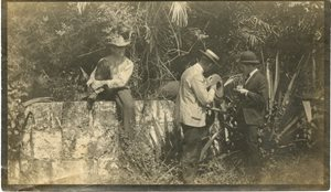 historic photo of men with cannon. 1 man sitting on wall, 2 men looking at cannon. overgrown plants around cannon