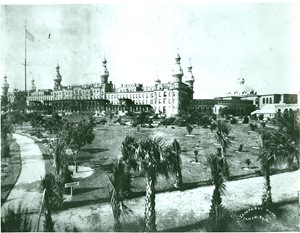 historic photo of Tampa Bay Hotel with gardens in foreground. American flag on flagpole in gardens