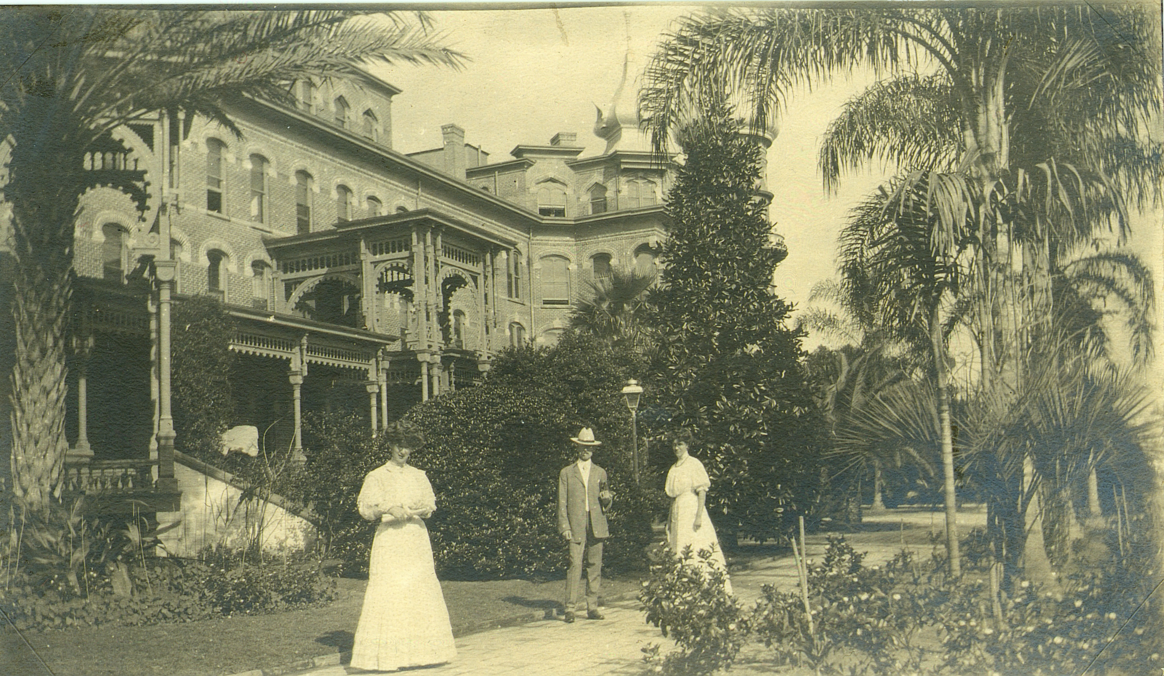 2 women and 1 man in old-fashioned clothing standing in front of hotel, surrounded by lush plants
