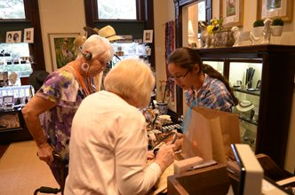 Volunteer and guests in museum store