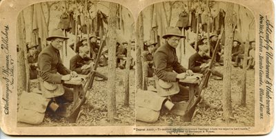 historic stereoscope card showing soldier, seated in forest, writing a letter, his gun propped up on a tree.