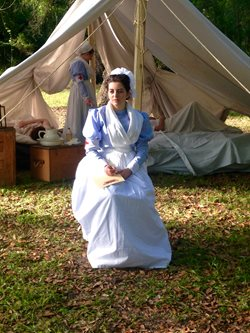 Young woman in historic nursing attire seated in front of 1890s style tent.