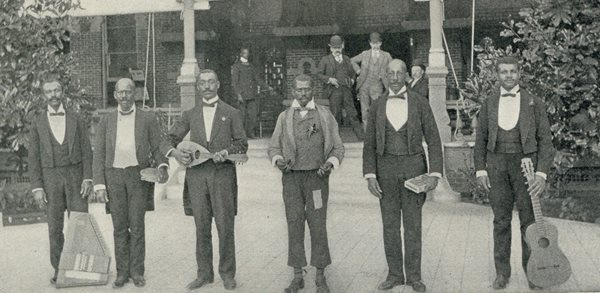 six dark skinned men in front of TBH, posing two feet apart, holding various instruments such as guitar, drum, mandolin. Dressed in minstrel suits with tails, ties and vests.