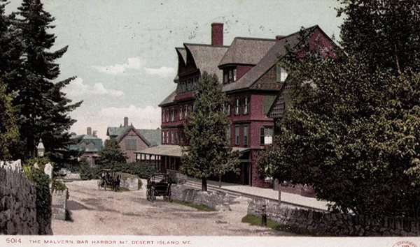 postcard of a four story red building, tall trees and stone fence along sidewalk