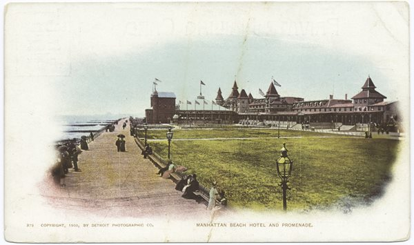 postcard of large building, flags flying, ocean coastline with large boardwalk bordering beach , people strolling and sitting on benches.