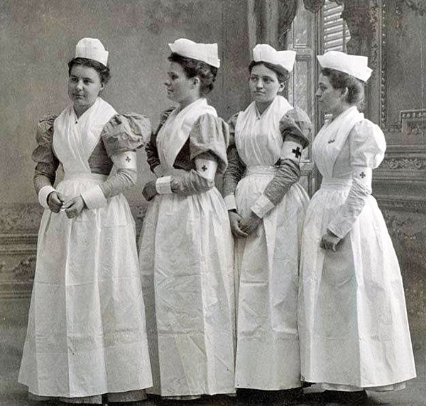 four young women standing dressed in uniform of white apron crossed in front, white folded hats, red cross on armband