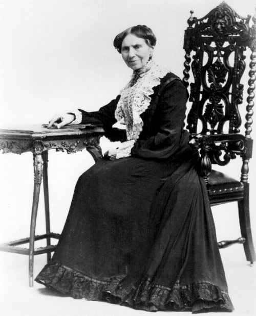 older Clara Barton in a dark dress with white lace front sitting on ornate wood chair leaning on table