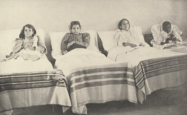 four children sitting up in hospital beds