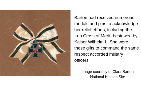 white silk ribbon bow with two black stripes tied with iron cross medallion decorated with small red cross. Caption: Barton had received numerous meals and pins to acknowledge her relief efforts, including the Iron Cross of Merit, bestowed by Kaiser Wilhelm I. She wore these gifts to command the same respect accorded military officers.