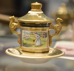 Small porcelain cup and saucer with lid gold trim and glazed image of woman playing tennis .Two opposing handles with winged dragons