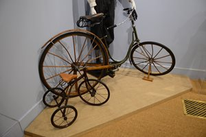 Ladies bicycle with wooden spokes and fenders next to child's tricycle