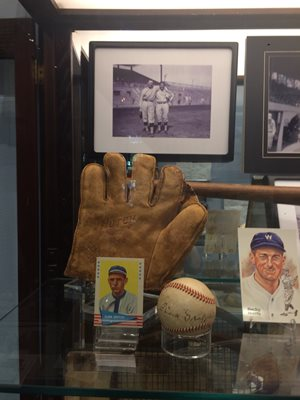 Partial display of baseball memorabilia: leather glove baseball cards photo of players signed baseball