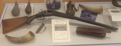 Case display of various artifacts: shotgun, horns, flask, game caller