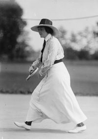 Frances Lippett in long white dress, white shoes dark belt, neck tie and hat swinging a tennis racket
