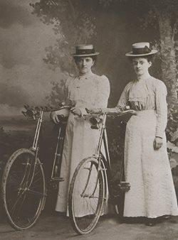 Two women wearing long dresses and hats standing next to bicycles with headlamps